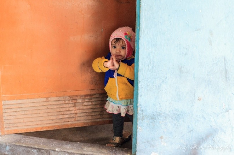 A baby girl in her mother's shoes looks out of a door above the spice market.