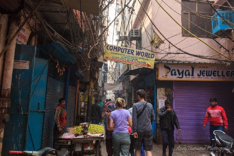 People walking through a busy alleyway in Old Delhi.