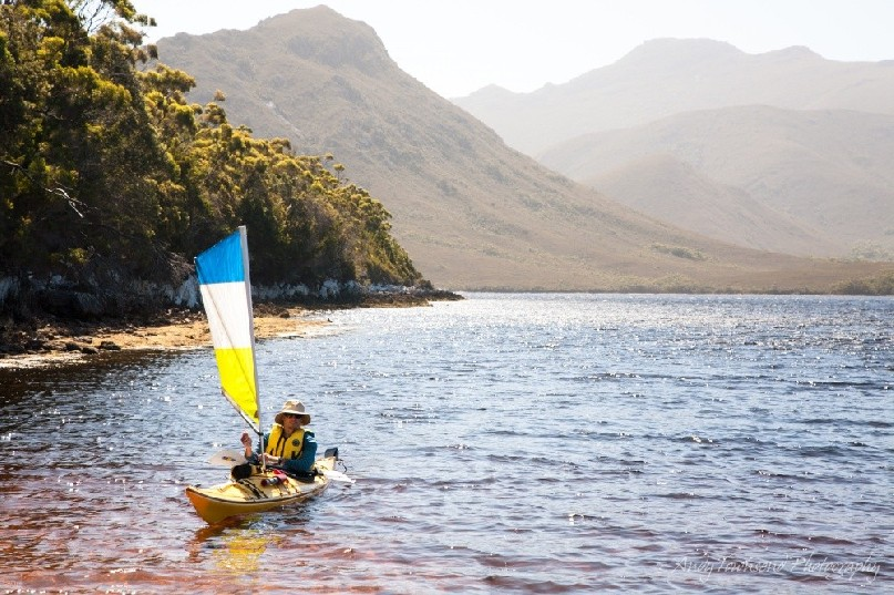 A sea kayaker under sail comes into land at a beach in Bathurst Harbour, Southwest Tasmania with peaks in the distance.