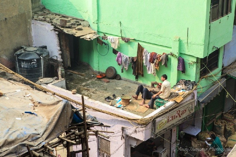 Two men relax on the roof enjoying a chat above the wholesale spice market.