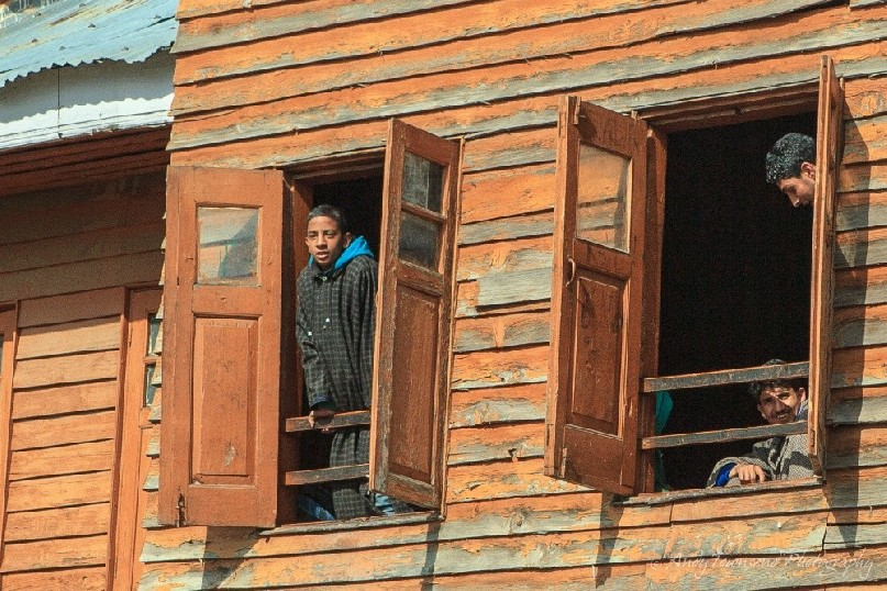 Three young Kashmiri boys framed in upper level windows at Babaeshi.