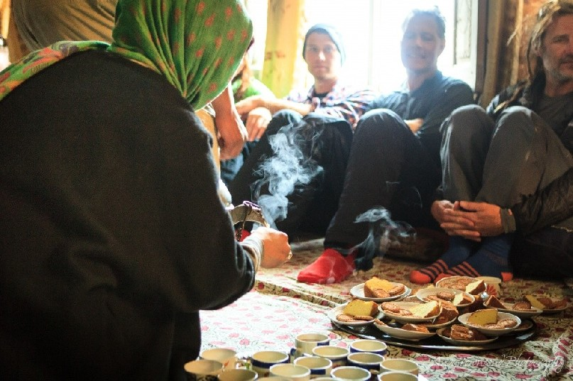 A lady pours sweet Kasmiri tea for a group of skiers in Drung village.
