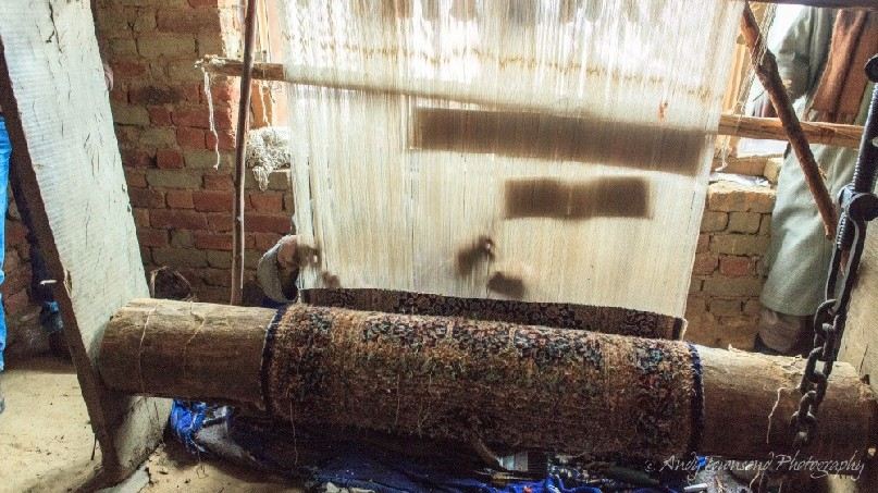 Two men work side-by-side weaving thread together to create a silk carpet - a 6 to 12 month process for one carpet.