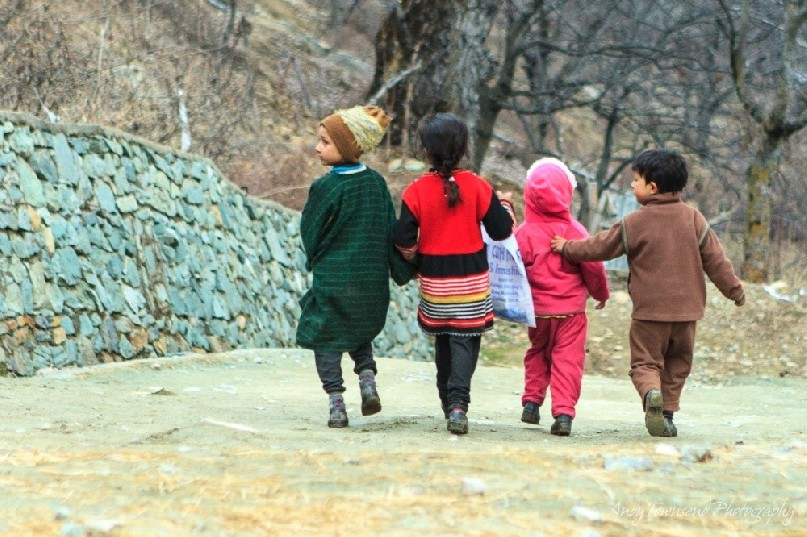 A group of four young children walk together, supportively, down a dirt path near Targmarg village.