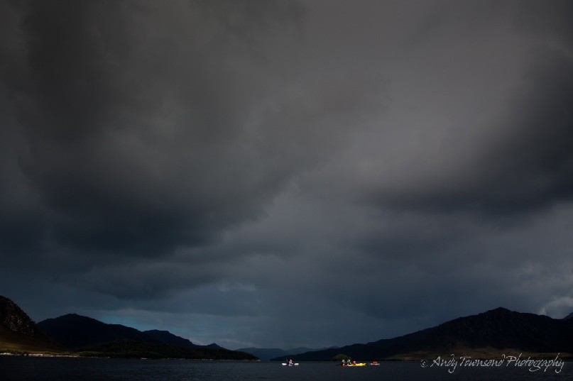 Storm clouds roll in over a group of sea kayakers in Bathurst Harbour, Southwest National Park, Tasmania.