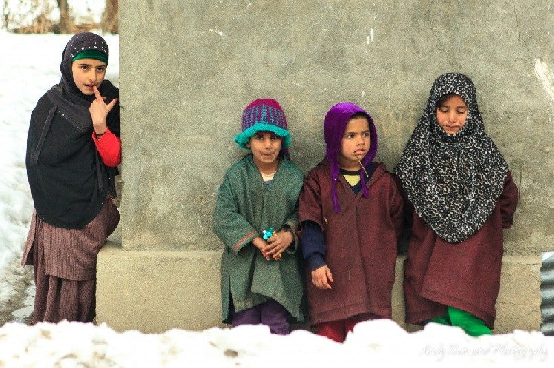 Four children leaning against a house wall in Drung village.