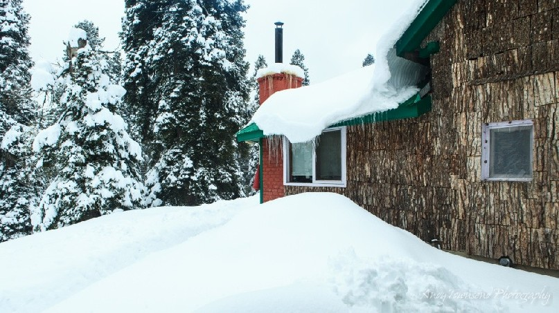 The exterior bark wall and chimney of one of the bedrooms in the hotel surrounded by deep snow.