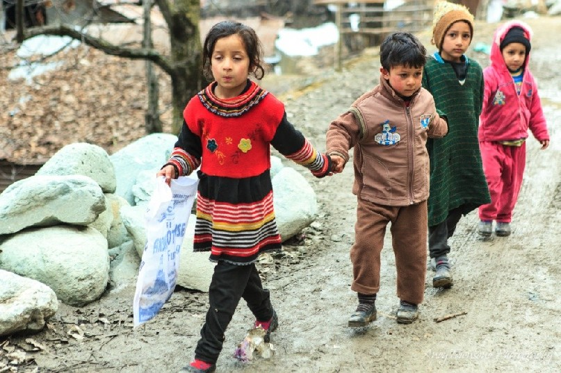 A group of four children walk hand-in-hand along a dirt track between Drung and Targmarg villages.