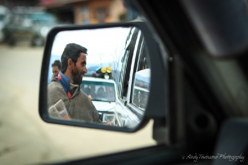 A Targmarg villager stops to sell his wares next to a vehicle window.