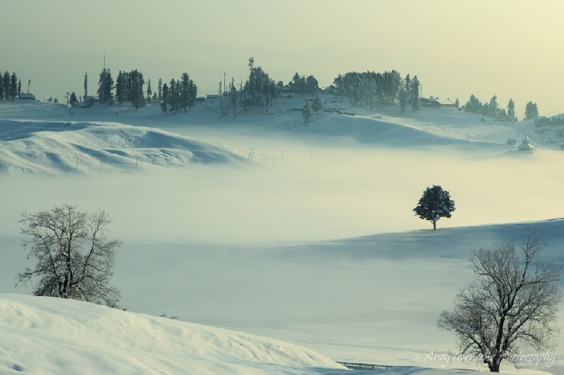 A layer of mist over covers the lower parts of Gulmarg.