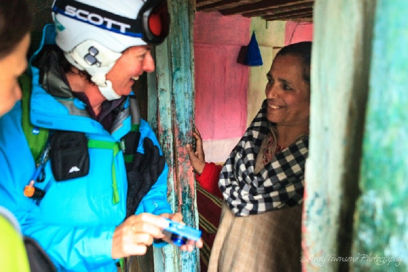 A female skier enjoys a moment showing a local Drung village woman a photograph she's just taken.