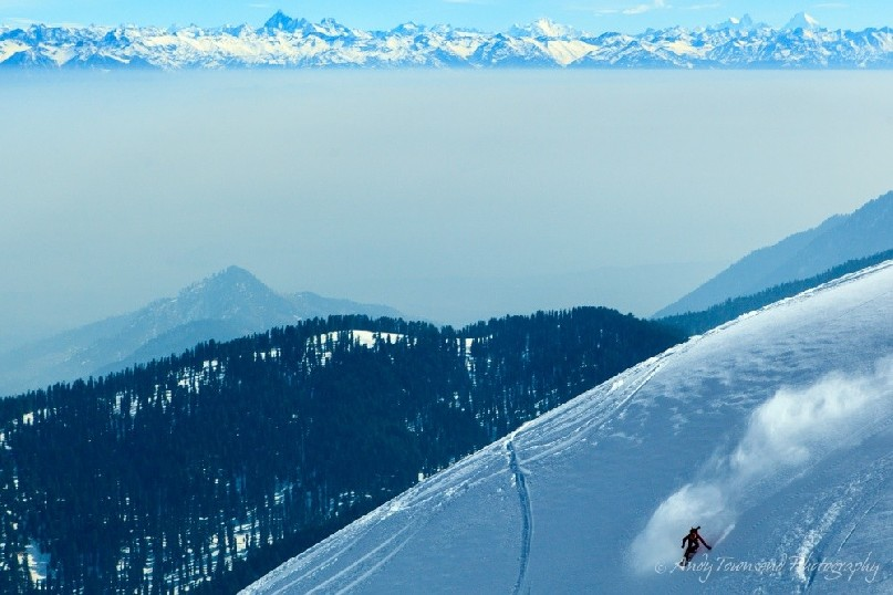 A snowboarder makes their way down an open ridgeline with the distant Himalayan mountains breaking through a layer of fog.