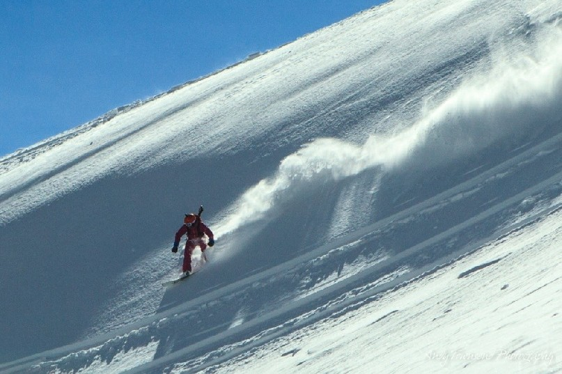 A plume of snow behind a snowboarder in the sunshine with blue sky.