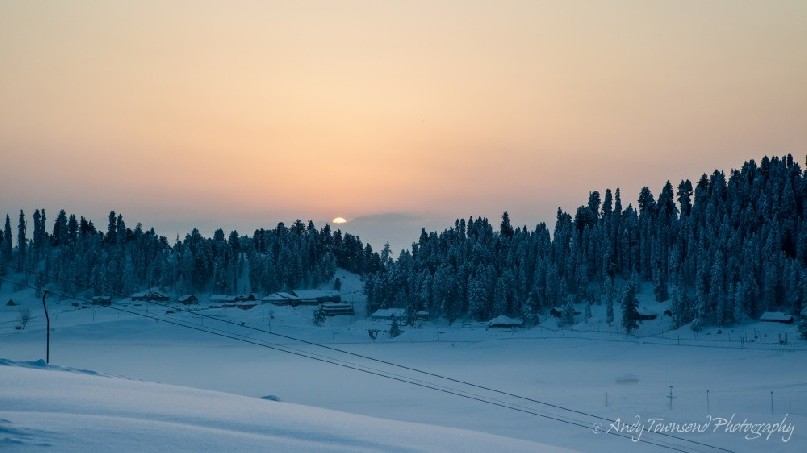 Sunrise breaking through a cloud band over a ridge of trees with fresh snow.