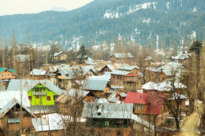 View over Tangmarg village with winter snow on the forested hillside behind.