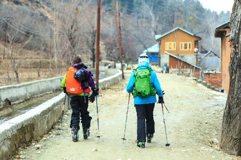 Two female skiers walking along a dirt track between Drung and Tangmarg villages.