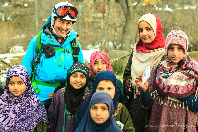 A female skier and a group of traditionally dressed young village girls pause for a portrait.