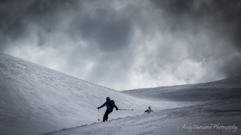 A female alpine skier making their way down an open slope with dark clouds above.