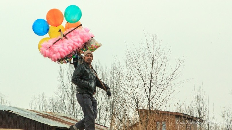 A man carrying a load of fairy-floss candy and balloons over his shoulder.