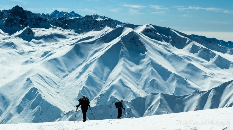 Two skiers skinning up towards the summit of Mt Apharwat with distant mountain range behind.