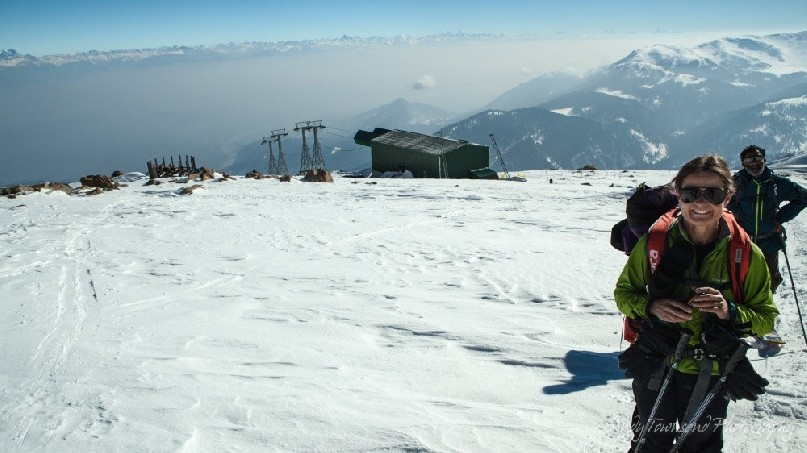 A women skier smiles above the top gondola station on Mt Apharwat in Gulmarg.