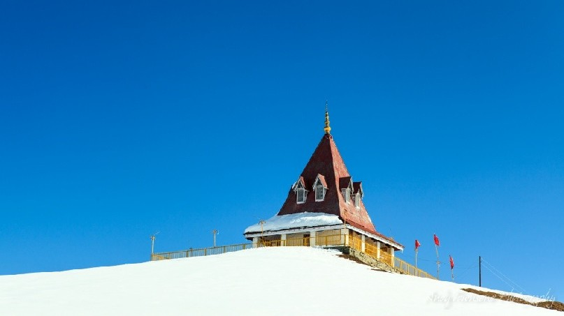 Looking up towards the Shiva temple surrounded by snow with a clear blue sky.