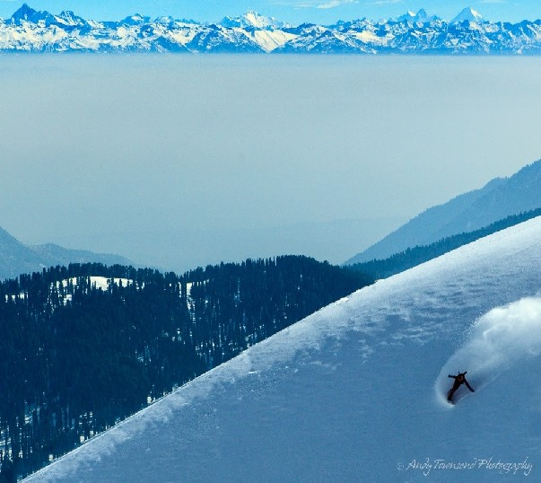 A snowboarder with plume of snow behind arcs down a slope with the distant Himalayan mountains behind.