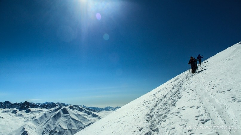 A group of skiers decent from the Shark's fin on a clear sunny day with peaks from the Pir Panjal Mountain Range beyond.
