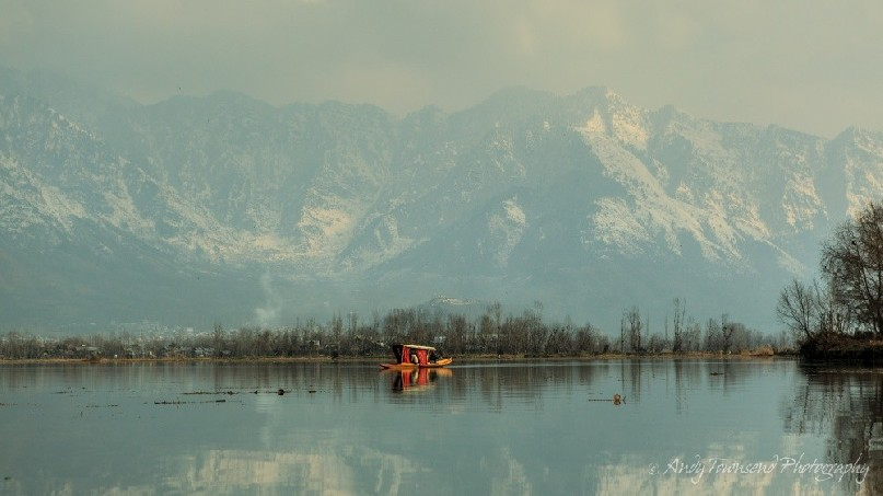 A distant shikara reflects in the stillness of Dal Lake with snow-covered mountains in the distance