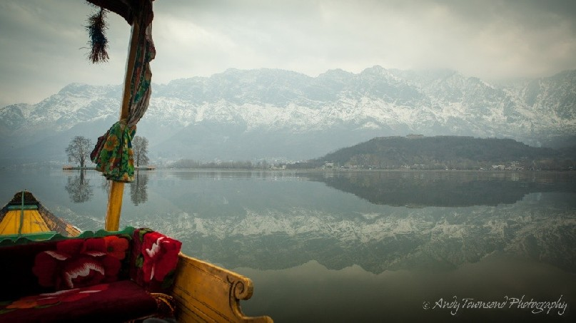 View from a Shikara out over the still waters reflecting the Zabarwan Range.