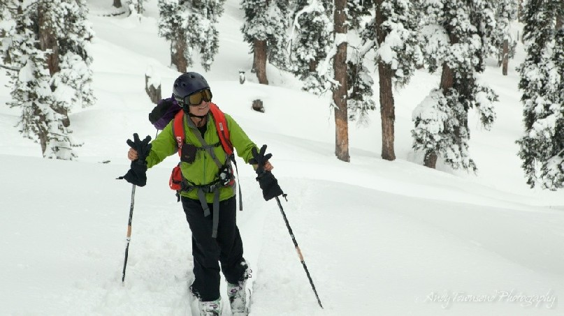 A smiling female skier skins up through a snow-covered forest.
