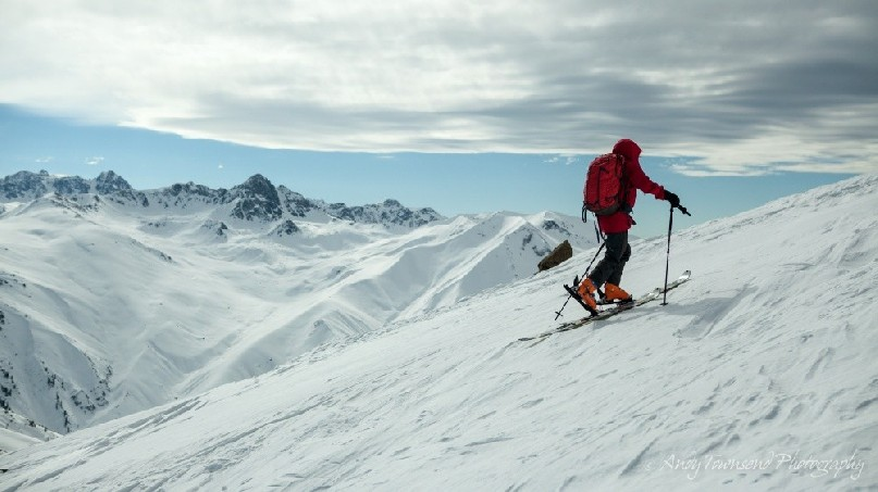 A skier skinning up towards the summit of Mt Apharwat with distant mountain range behind.