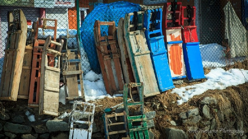 A line of colourful sleds lie against a fence in Gulmarg village.