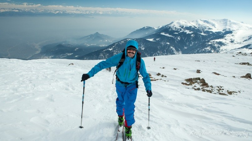 A smiling skier makes their way towards the summit of Mt Apharwat with distant fog in the valley below.
