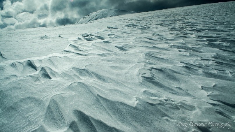 A line of wind-sculpted snow leads to a distant peak beyond.
