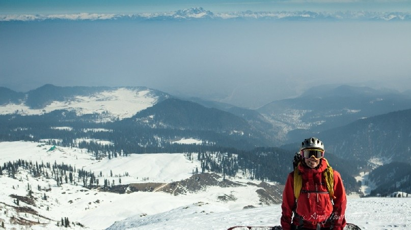 A female snowboarder pauses atop a ridge with distant fog in the valley behind and mountains of the Himalaya above.