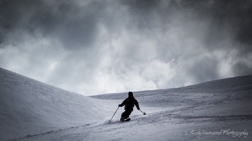 A female telemark skier in mid-turn makes their way down an open slope with dark clouds above.