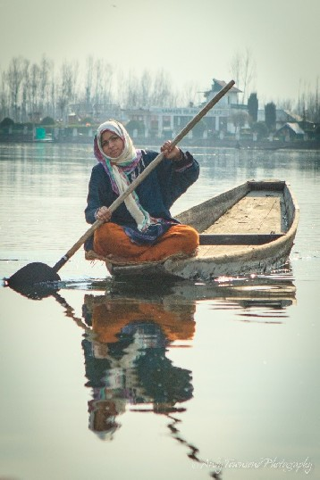 A young woman balances elegantly on the edge of a  wooden boat in Dal Lake.