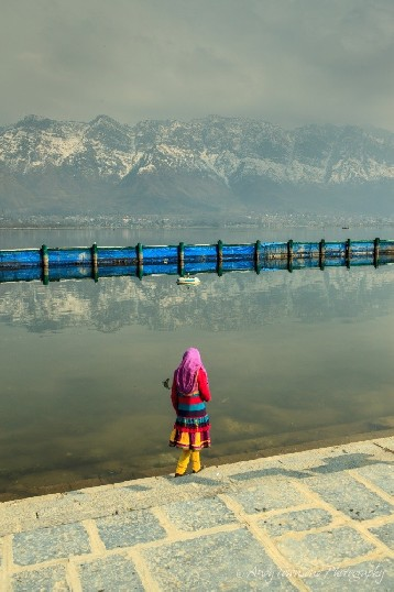 A young girl in colorful dress pauses on the steps with snow-covered mountains in the distance.