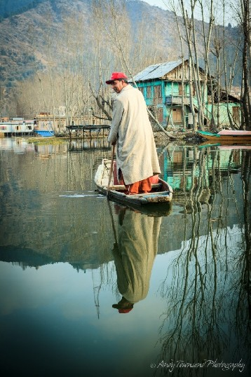 A man standing in a wooden boat wearing traditional phiren is reflected into the still waters of Dal Lake.