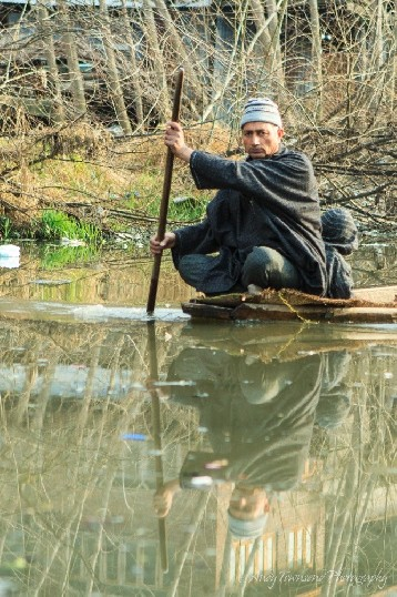 A man blances on the edge of his wooden boat navigating a channel off Dal Lake.