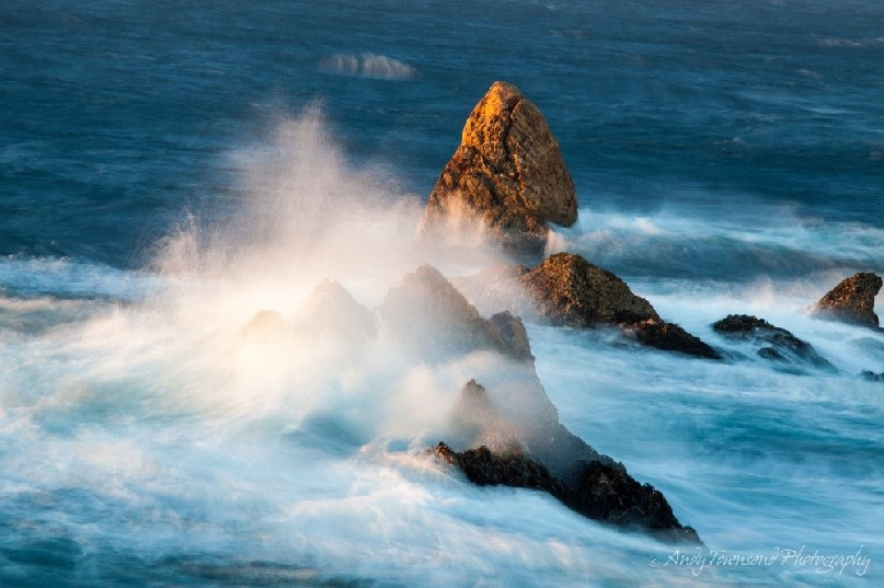 A small sea-stack on the Tarkine coast catches the last of the sun's rays as a wave crashes over it.