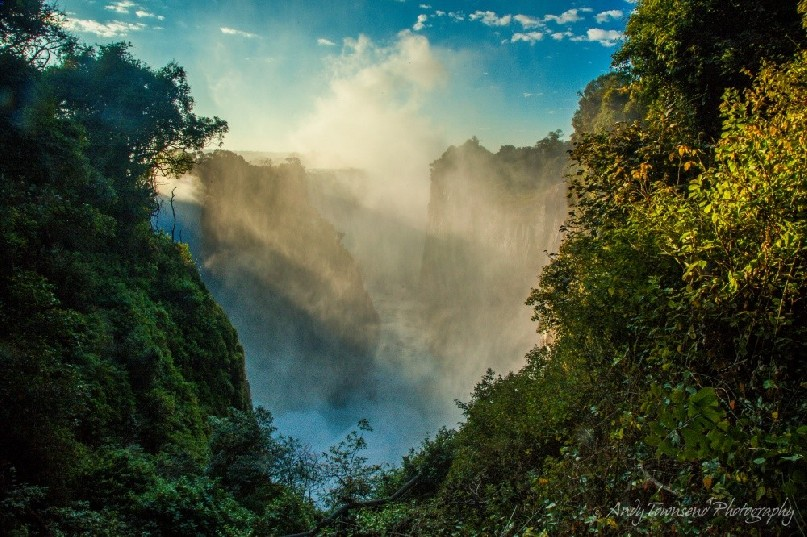 Sunlight on the vegetated cliffs surrounding Victoria Falls with mist from the falls rising in the distance.