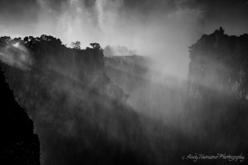 Sunlight filters through the mist and spray from Victoria Falls.