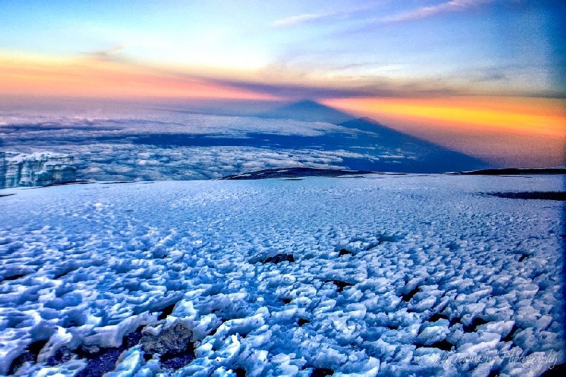 Early morning light from Mt Kilimanjaro summit with ice in the foreground and the shadow of the mountain above Mt Meru in the distance.