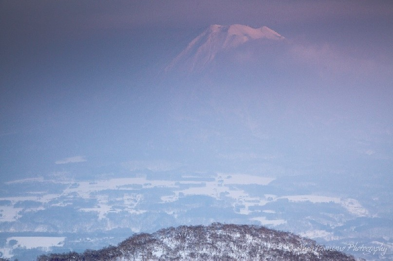 As a light mist decends into the valley, the distant summit of Mt Yotei catches the last light of the day